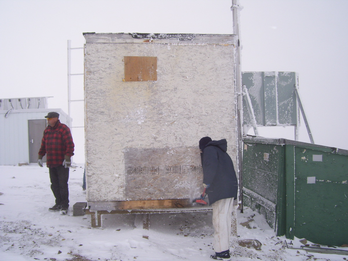 Scraping the ice off the building.